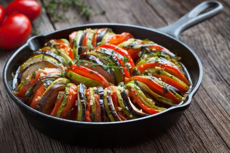 Traditional homemade vegetable ratatouille baked in cast iron frying pan healthy diet french vegetarian food on vintage wooden table background.