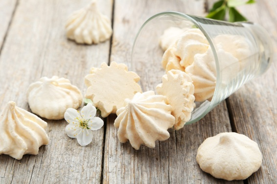 French meringue cookies with glass on grey wooden background