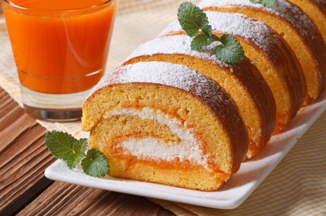 Tasty dessert of pumpkin roll with cream closeup