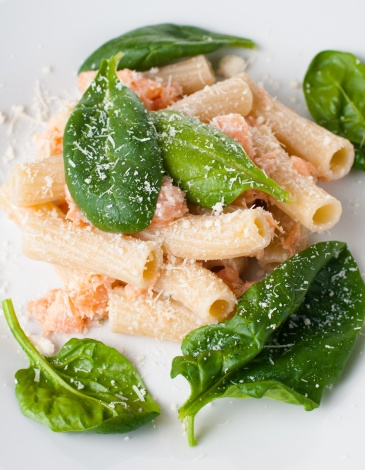 Pasta with salmon and spinach, portion of rigatoni with seafood and parmesan cheese, Italian food, isolated on white background