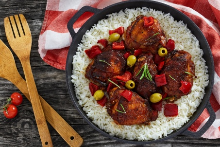 rice with grilled chicken thighs, red bell pepper, green olive and rosemary in cast iron stewpan with kitchen towel on wooden table, mediterranean cuisine, view from above