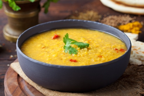 Red lentil Indian soup with flat bread on a wooden background. Masoor dal