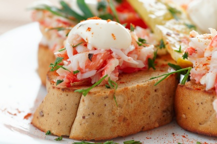 Crab meat with toast, sauce and fresh herbs, close-up