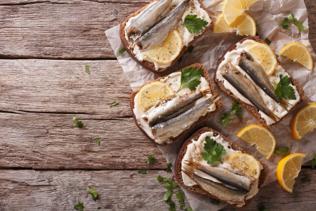 Toasts with sprats, cream cheese and lemon horizontal top view