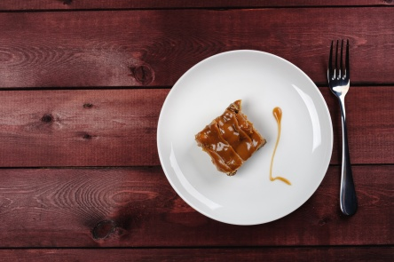 a piece of tasty chocolate brownie and caramel sauce on a white plate on a wooden table. Top view