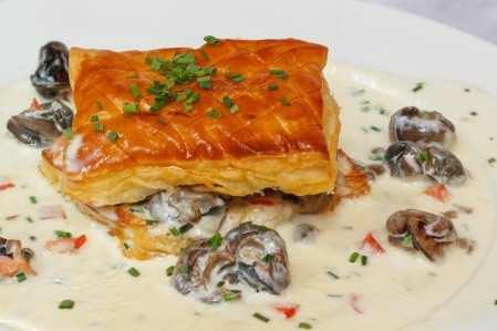 Snails in creamy sauce with puff pastry cookies. French gastronomic cuisine