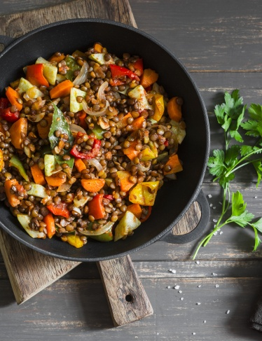Lentils and seasonal garden vegetables braised in the pan on wooden background, top view. Autumn vegetarian healthy lunch