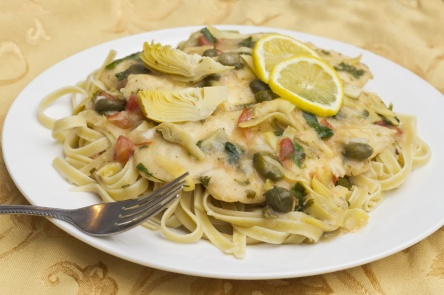 Italian chicken piccata schnitzel with artichoke hearts served on linguine