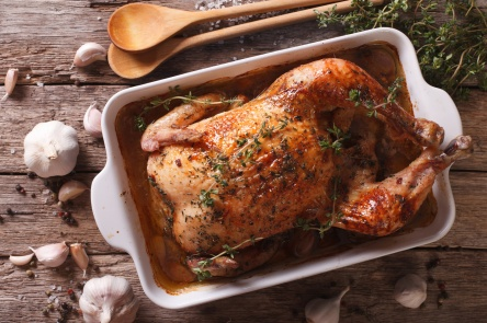 French cuisine: Chicken with forty cloves of garlic close-up. horizontal top view