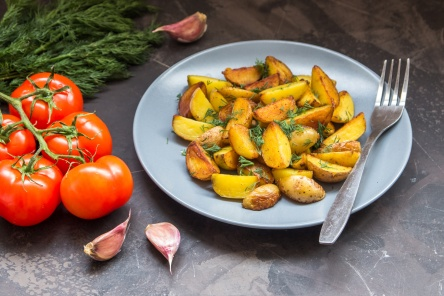 Fried baby potatoes, green, tomatoes and garlic on a dark background.