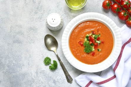 Tomato soup gazpacho or salmorejo in a white bowl on a light slate,stone or concrete background.Top view with copy space.