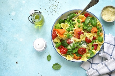 Pasta primavera with spring vegetables in a white vintage bowl on a light blue slate, stone or concrete background.Top view with copy space.